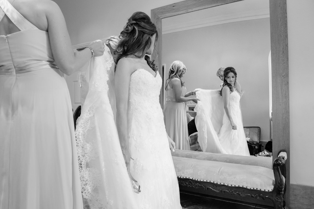 Bride putting her wedding dress on at Notley Abbey