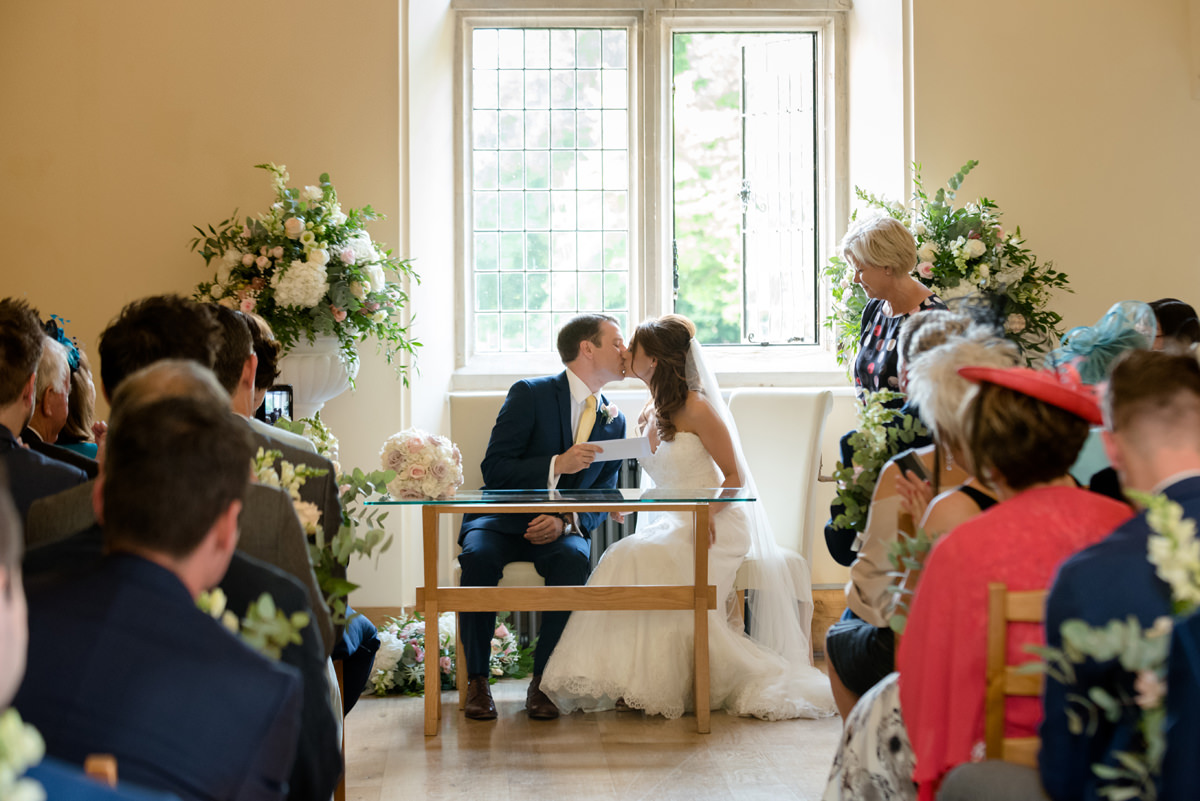 Bride and groom kiss as they receive their marriage certificate at Notley Abbey