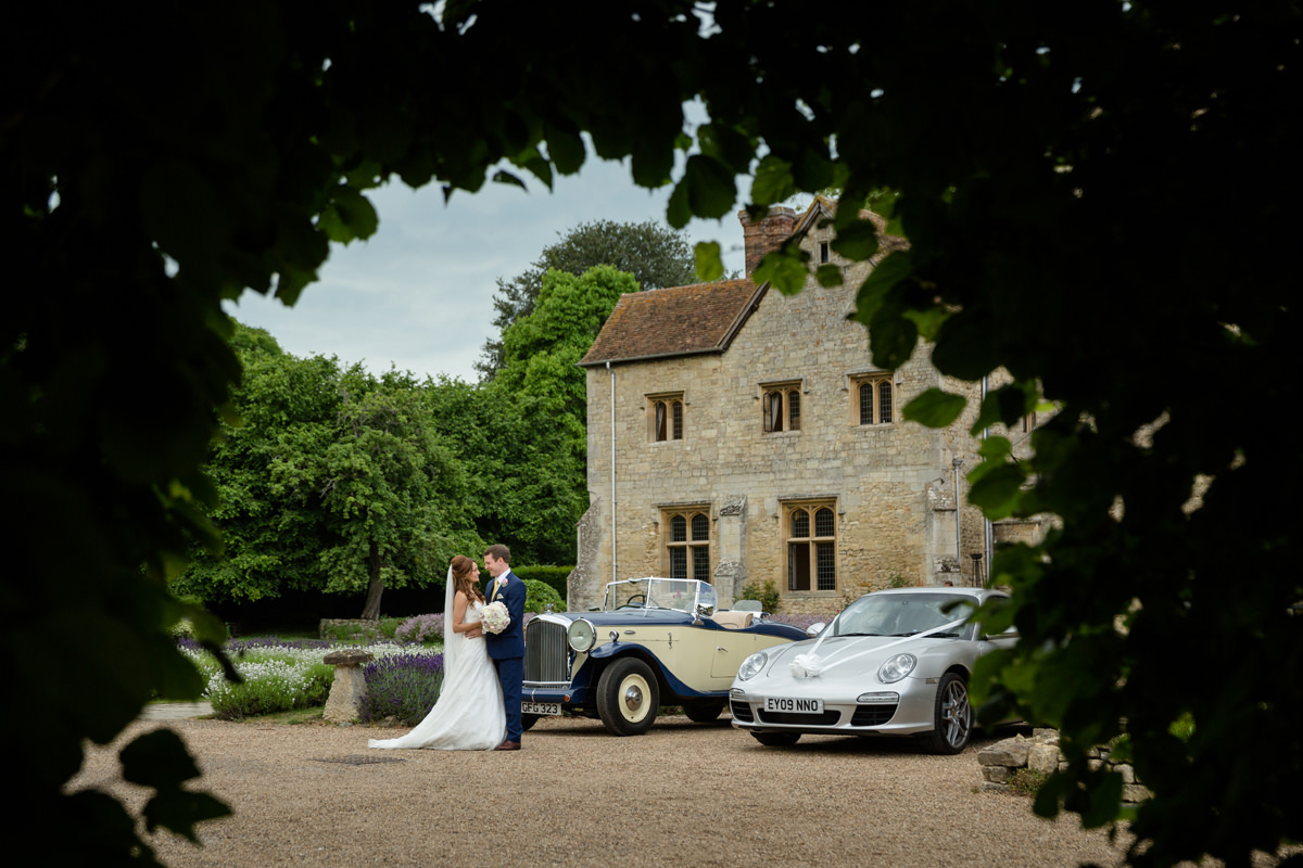 Bride and groom with their wedding cars at Notley Abbey