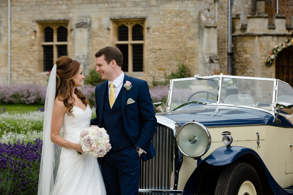Bride and groom with a vintage wedding car at Notley Abbey