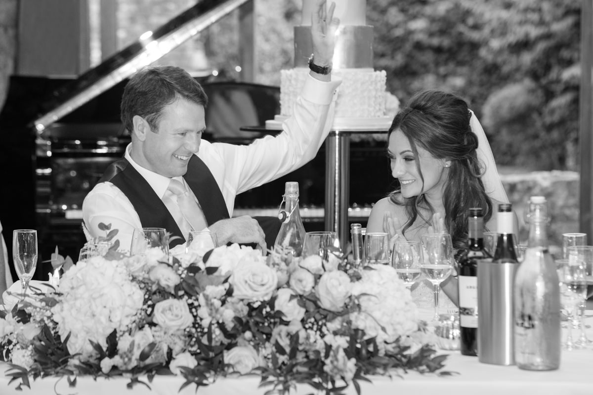 Bride and groom laughing during the speeches at Notley Abbey
