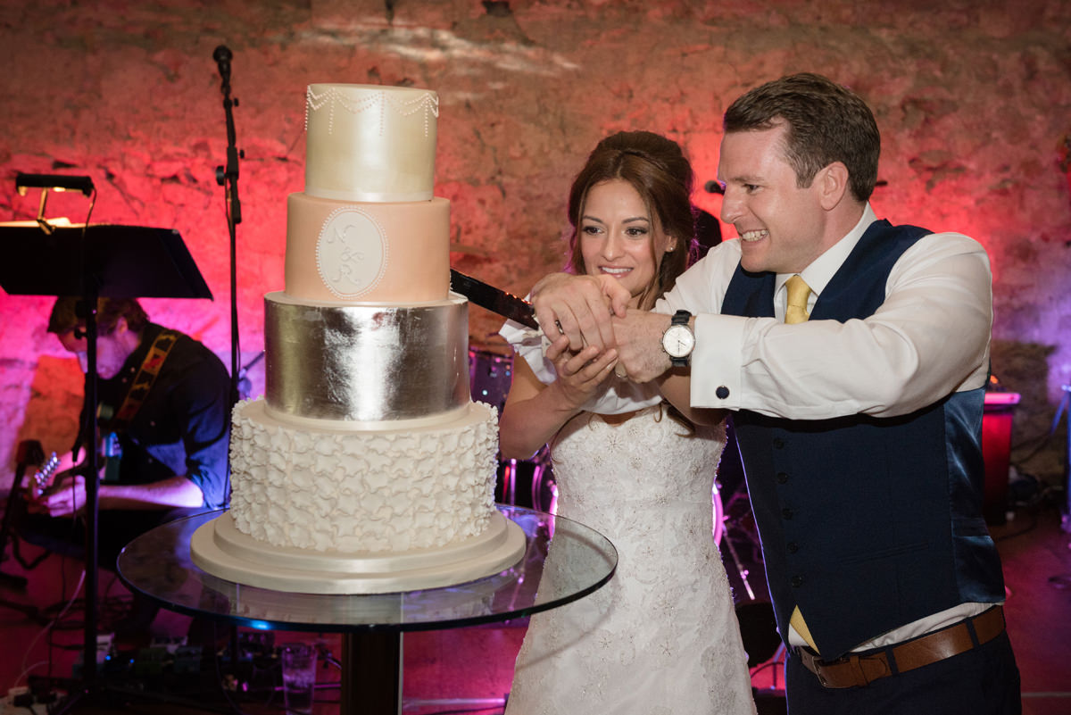 Bride and groom cutting their wedding cake at Notley Abbey