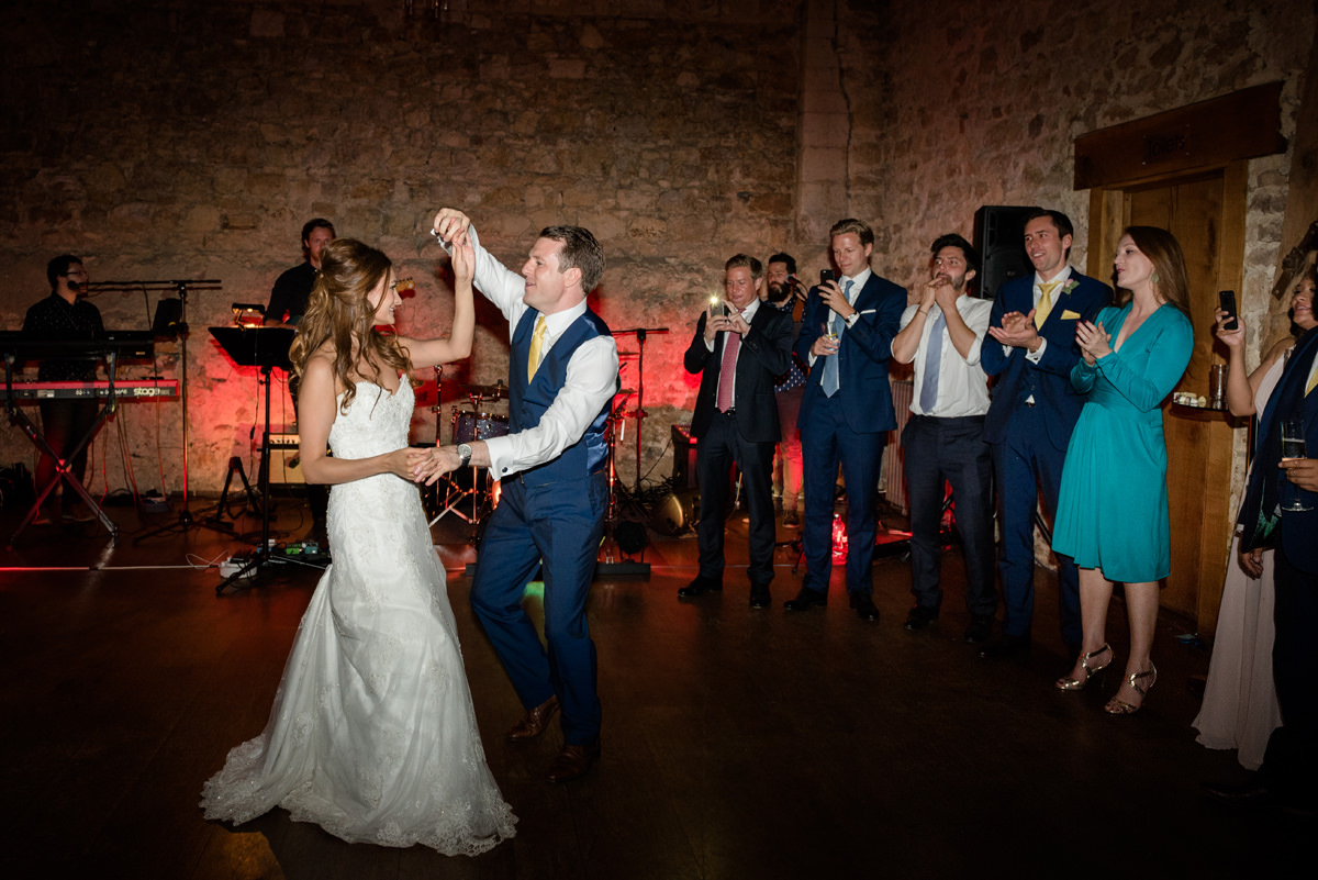 Groom twirling the bride during their first dance at Notley Abbey