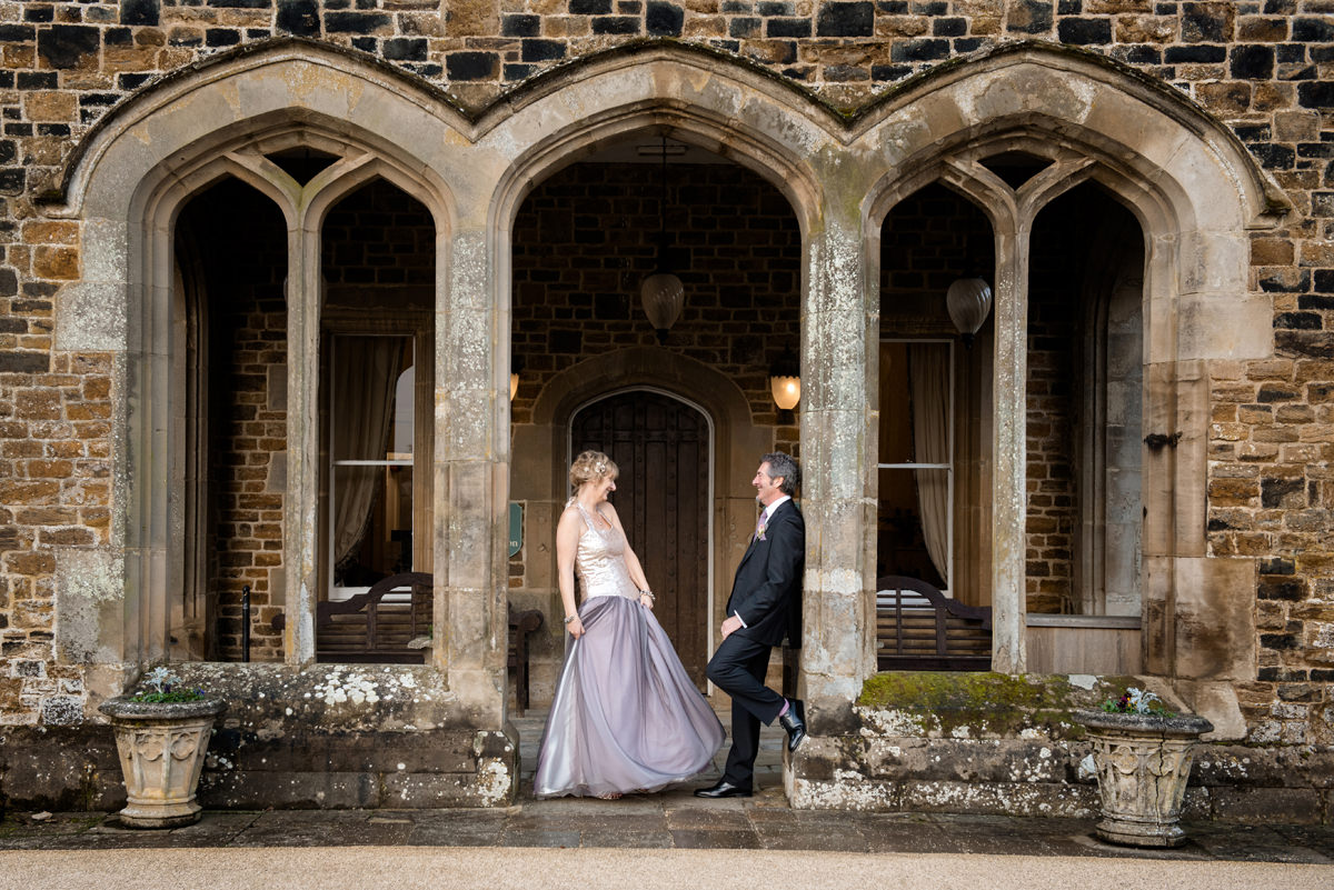 Portrait of a bride and groom at the entrance to Fawsley Hall