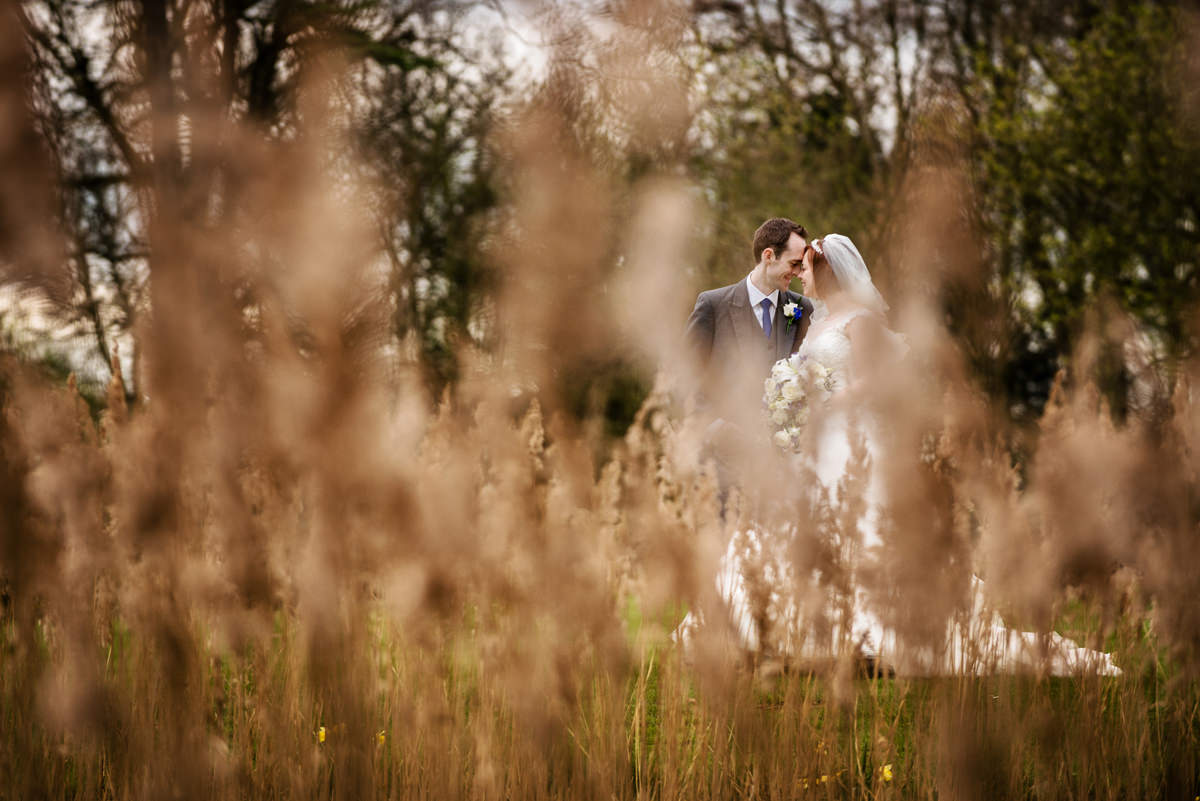 Photo of a bride and groom through long grasses at Chicheley Hall