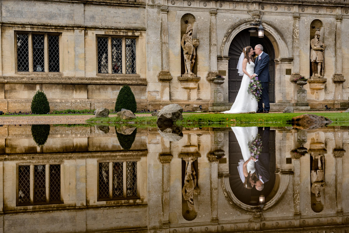 Reflection of a bride and groom in a puddle at the entrance to Rushton Hall