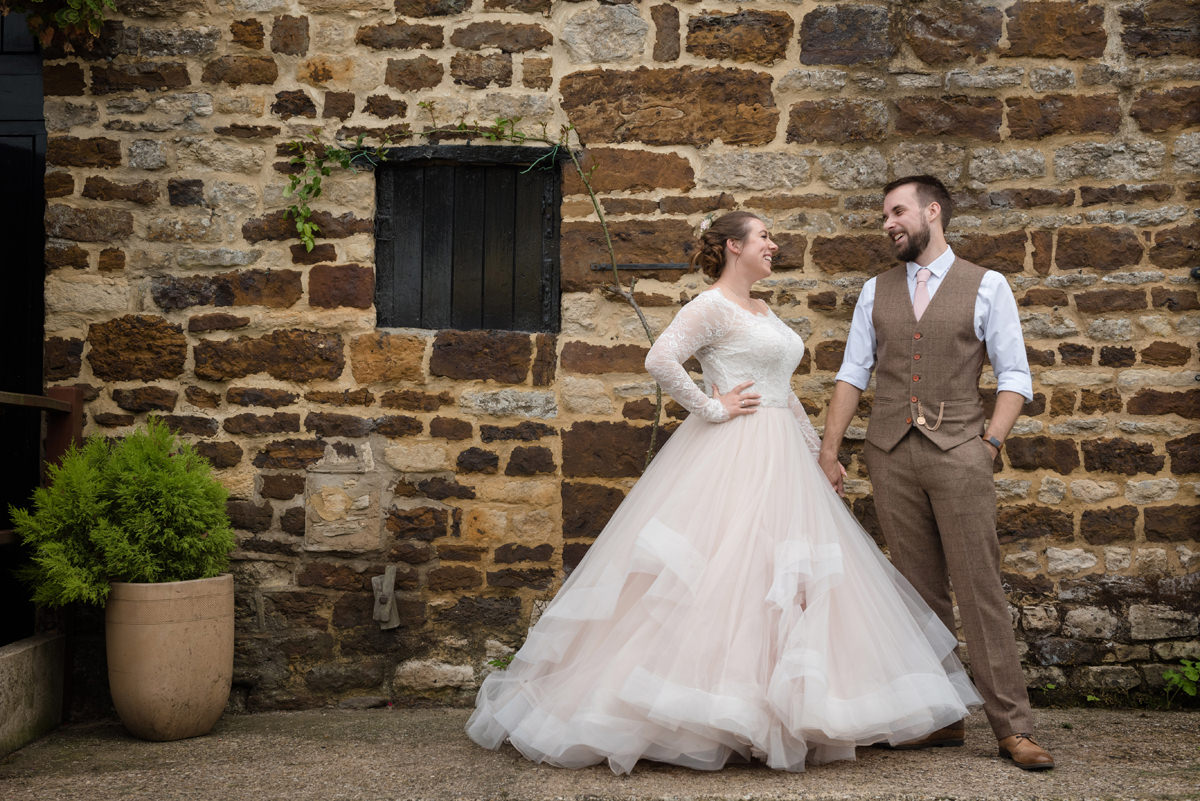 Portrait of a bride and groom against a rustic wall