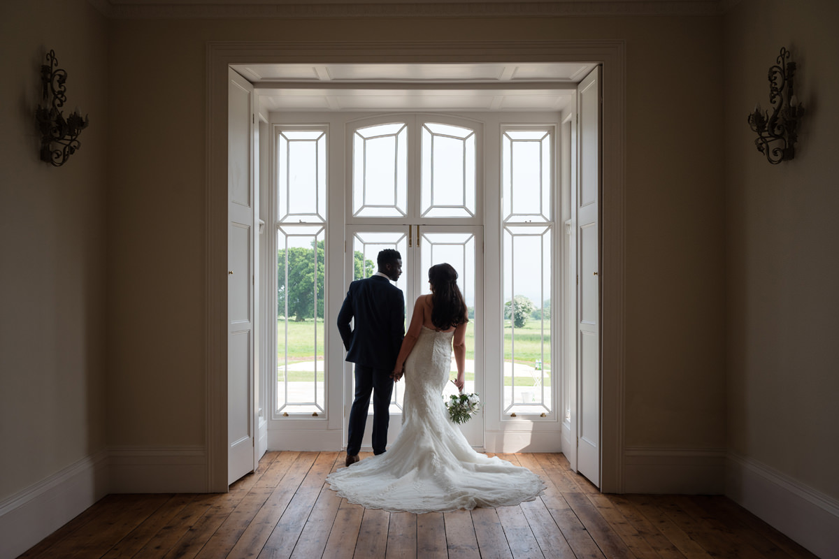 Portrait of a bride and groom in a bay window at St Tewdrics House
