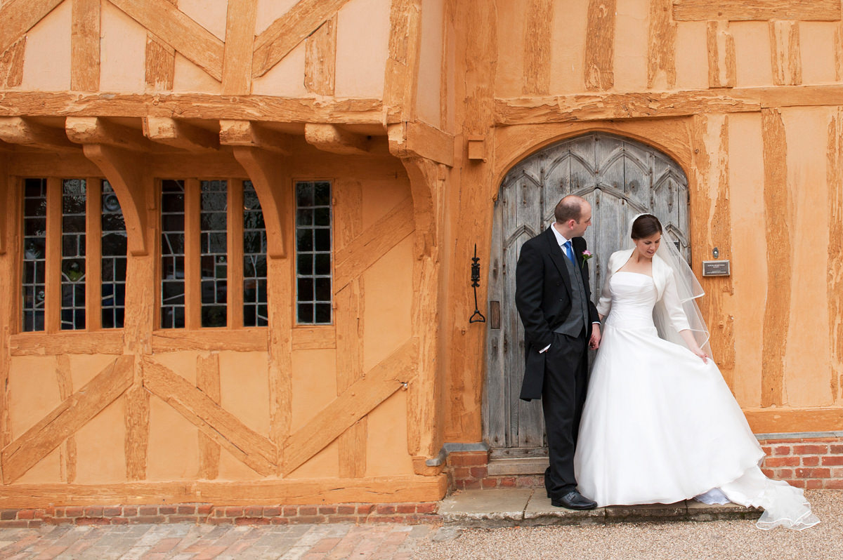 A bride and groom standing in front of a timber framed house in Lavenham