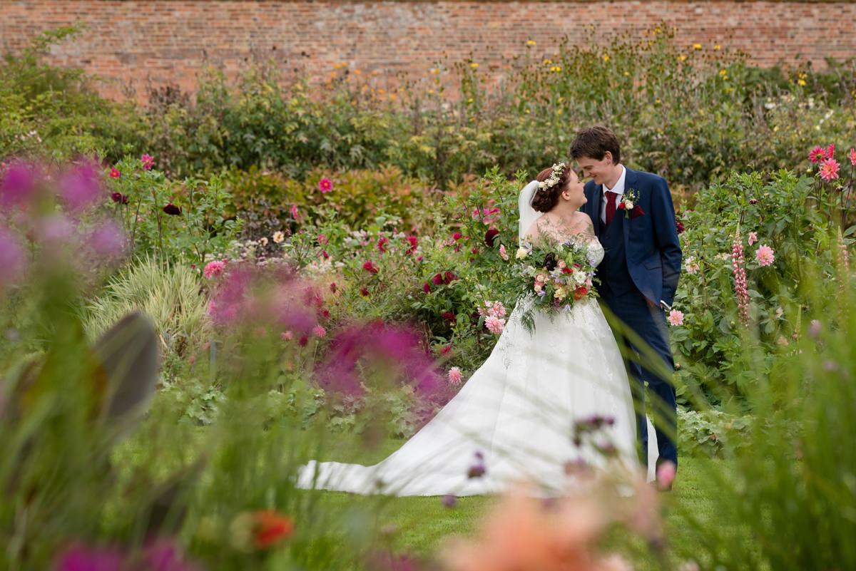 Portrait of a couple in a walled garden surrounded by dahlias at Kelmarsh Hall