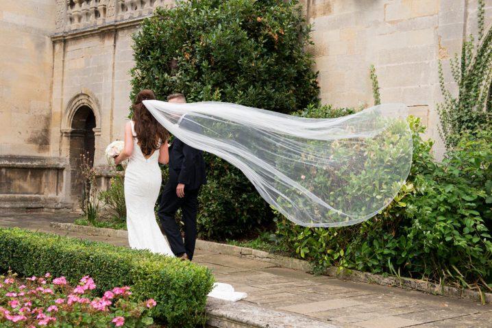 Bride's veil flying behind her as she walks with her groom