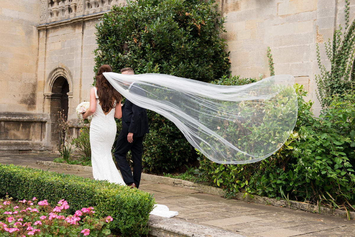 Bride's veil flying behind her as she walks with her groom
