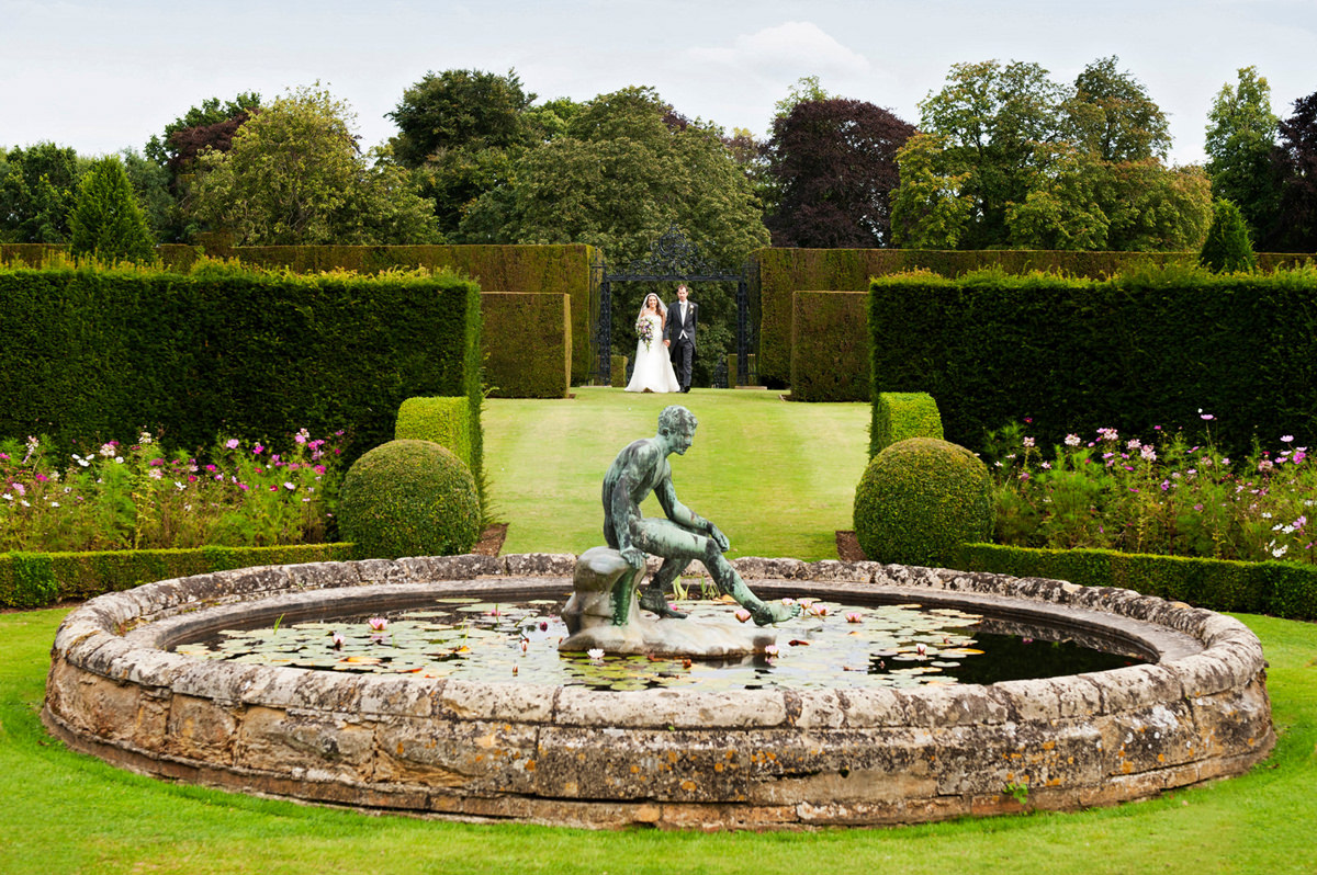 Portrait of bride and groom walking in the lily pond garden at Holdenby House