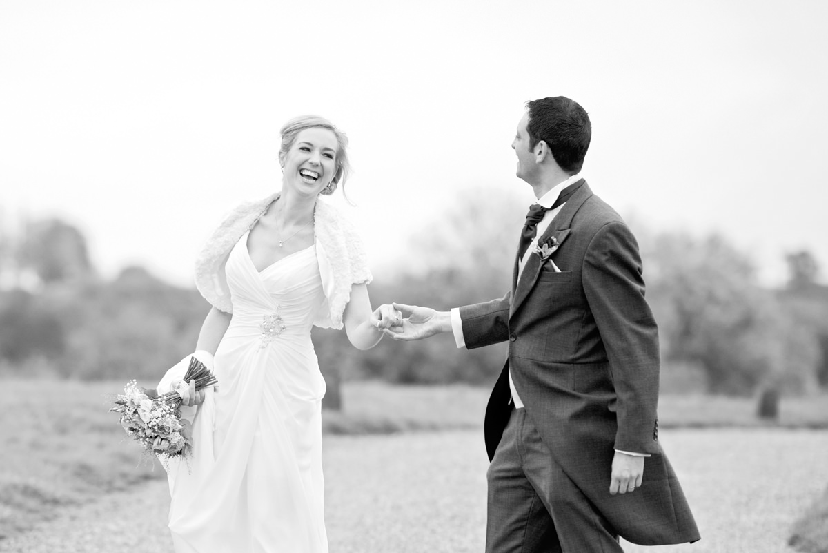 Bride and groom laughing as they walk for their couple portraits