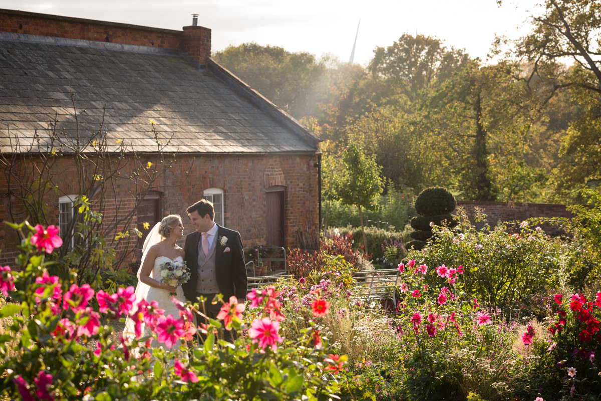Bride and groom walking in a walled garden during golden hour