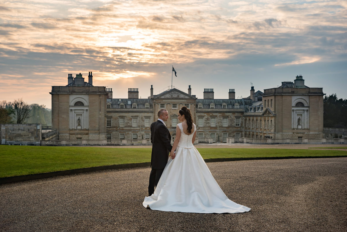 Portrait of a bride and groom in front of Woburn Abbey at sunset