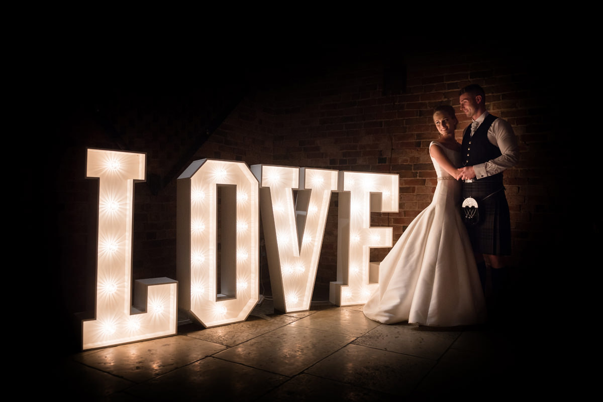 Portrait of bride and groom with light up LOVE letters