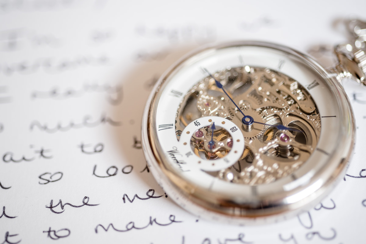 A groom's pocket watch on a wedding card from the bride
