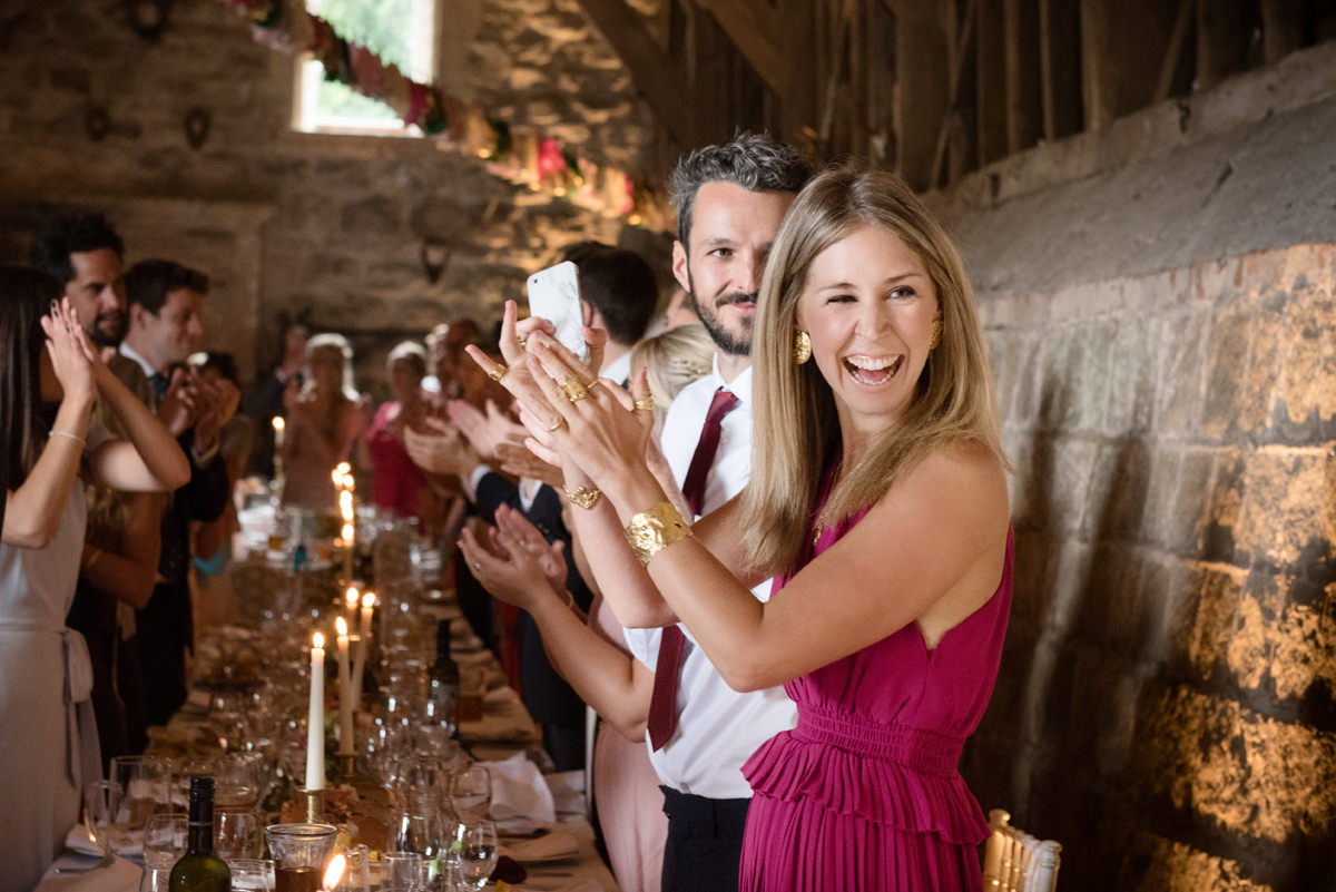 Wedding guests clapping as the bride and groom are announced into dinner