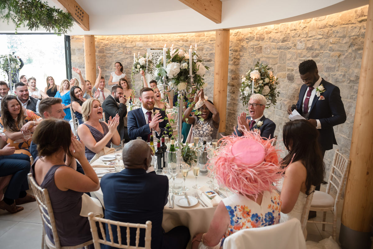 A room full of wedding guests cheering as the groom mentions the word 'wife'