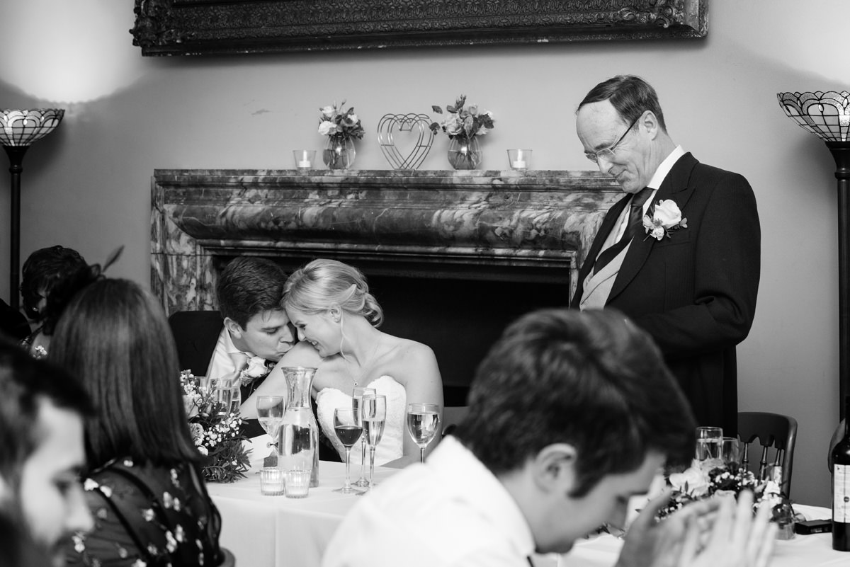 The groom kissing the bride's shoulder during the speeches