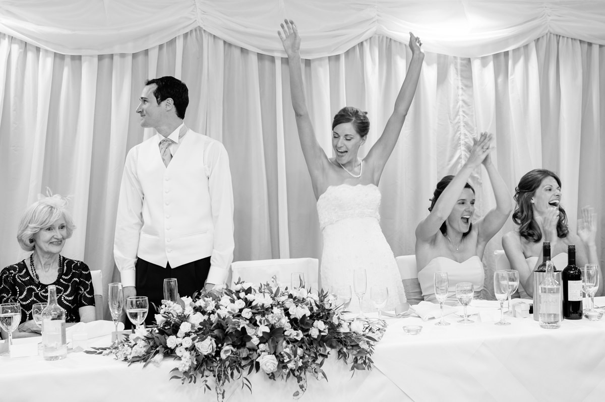The bride cheering during the groom's speech