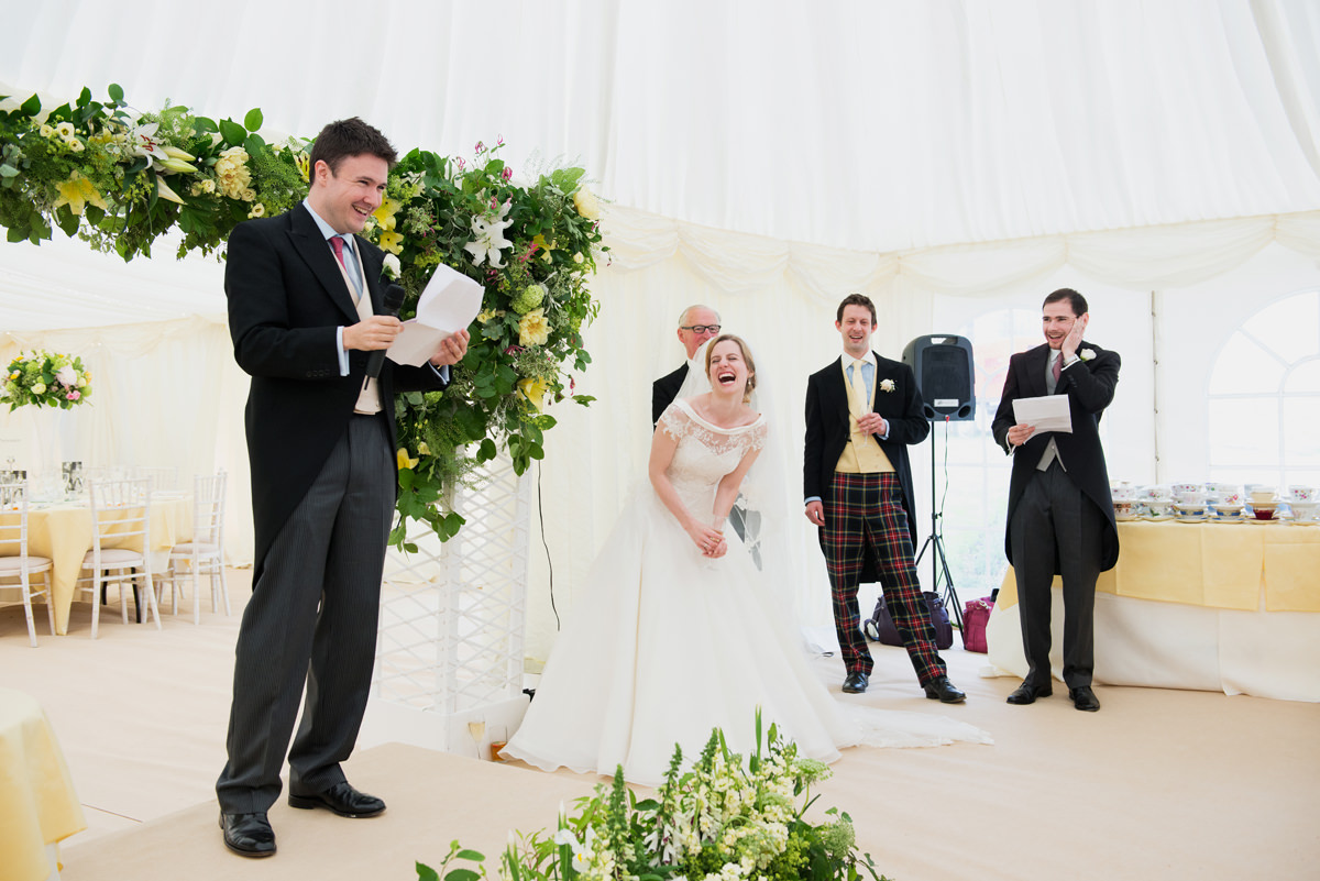 Bride doubled over laughing at the groom's speech