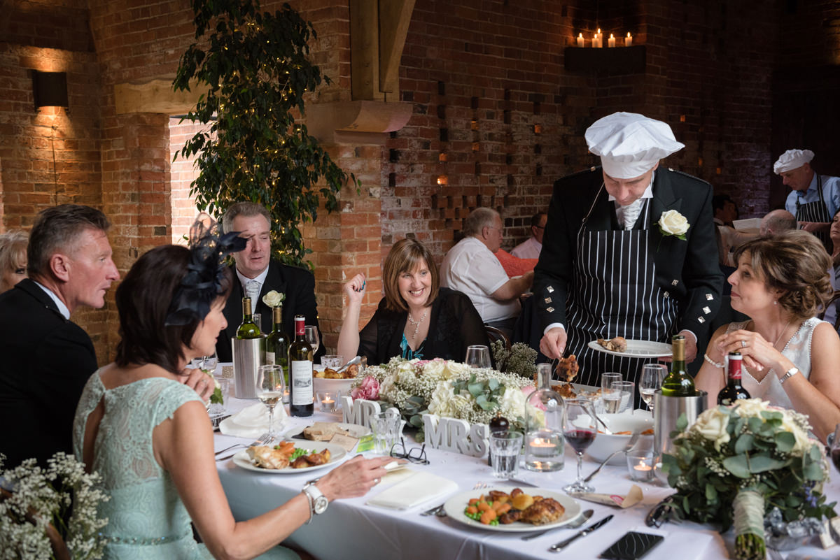 Wedding guests serving roast chicken at the table in a chefs hat