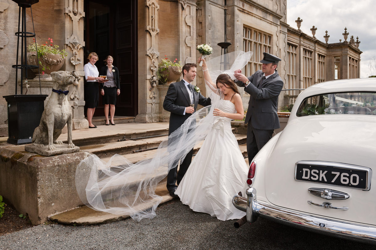The bride's veil blowing in the wind as she arrives at Stoke Rochford Hall for the drinks reception
