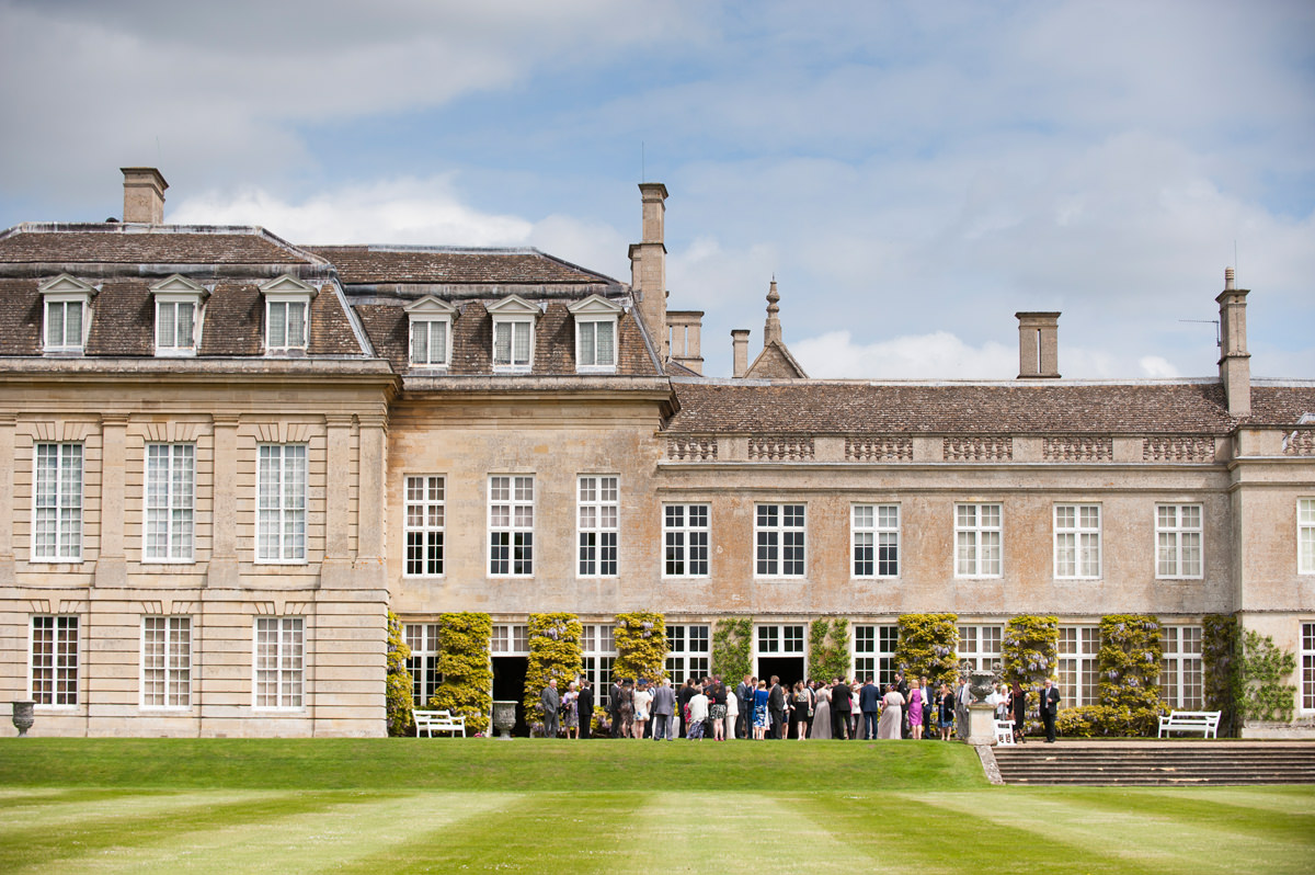 Wedding guests on the west front at Boughton House during the drinks reception