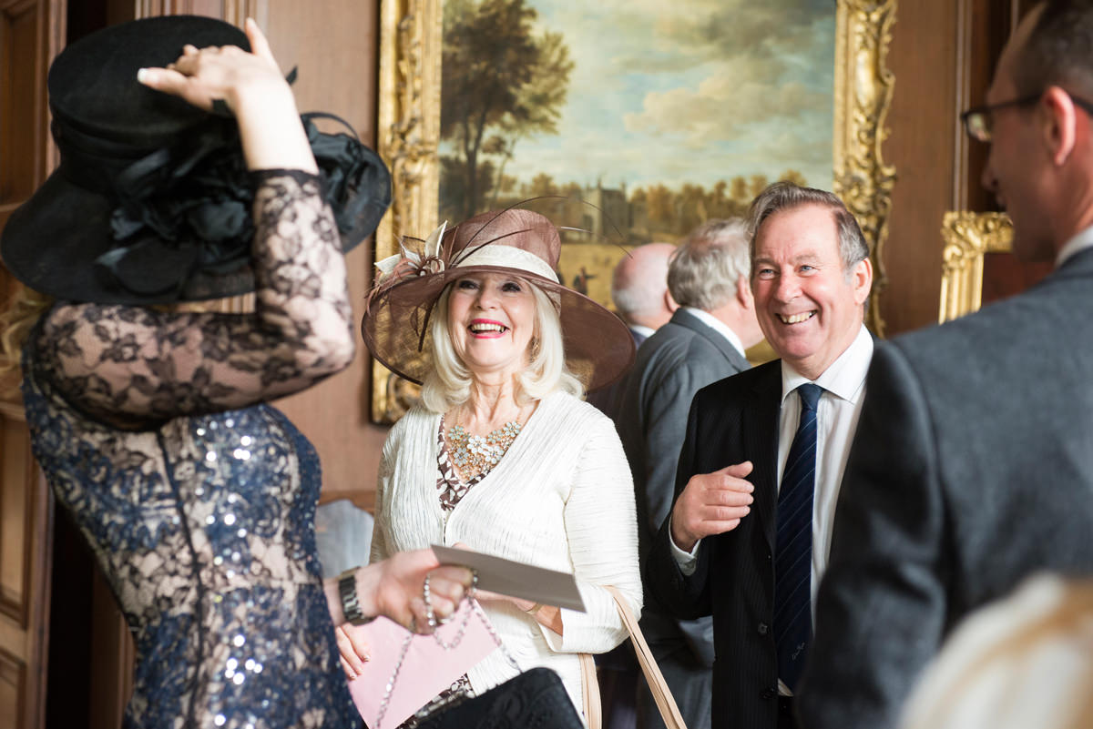 Wedding guests laughing during the drinks reception at Boughton House
