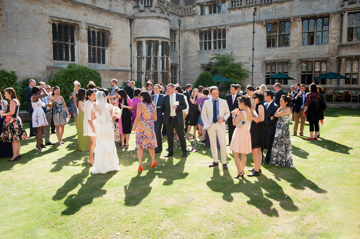 A sunny wedding drinks reception in the courtyard at Rushton Hall