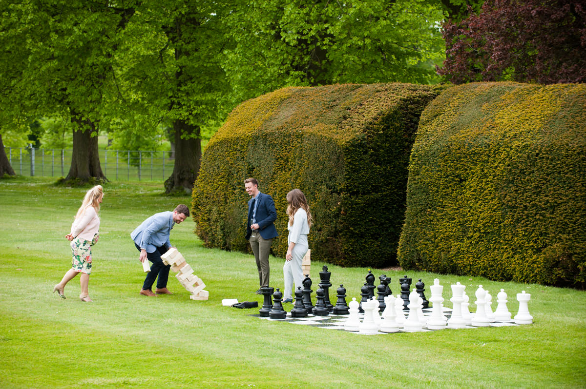 Wedding guests playing giant jenga in the gardens at Boughton House