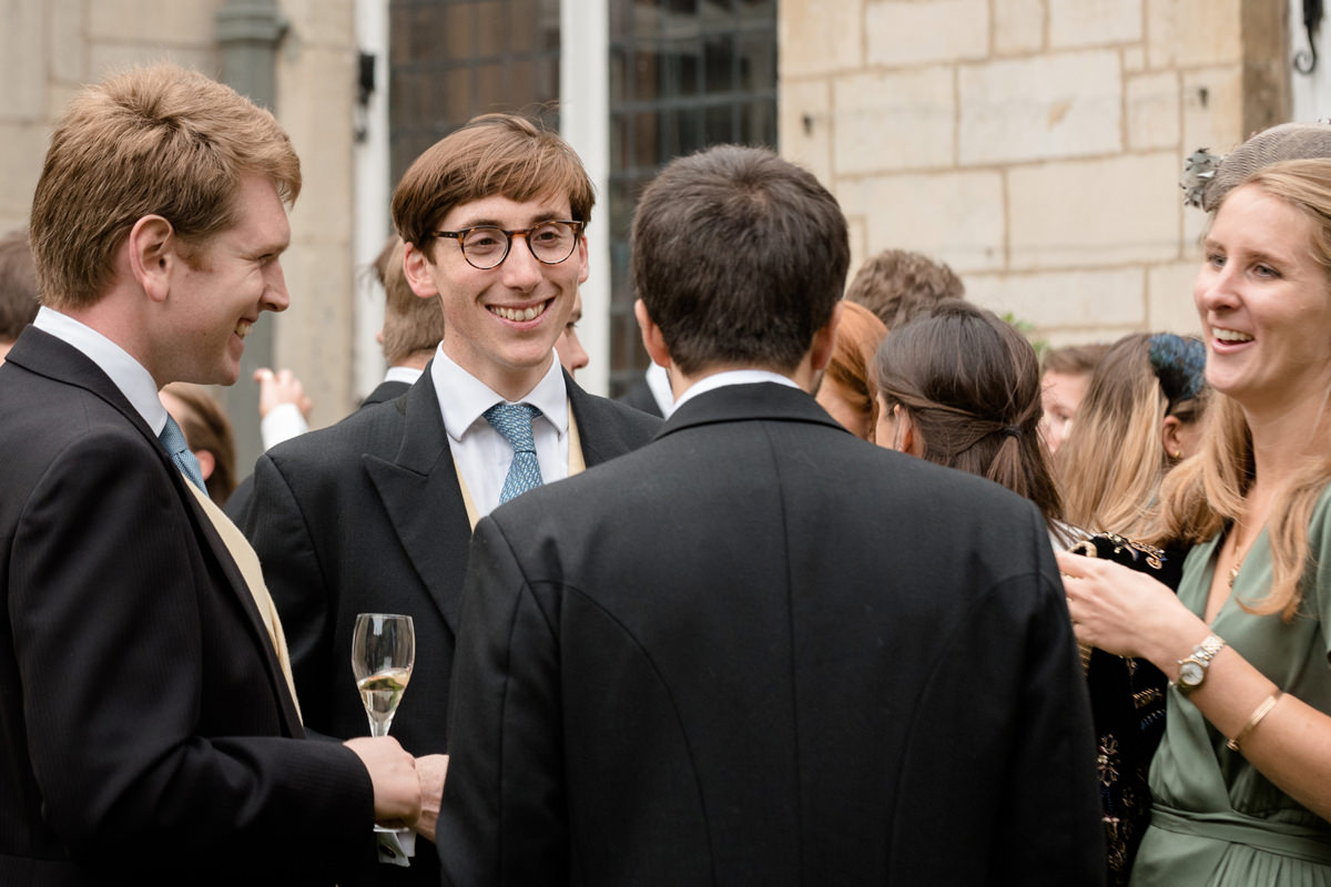 Wedding guests chatting during the drinks reception at Boughton House