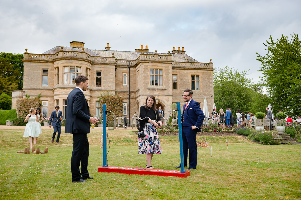 Wedding guests playing giant garden games outside Wadenhoe House