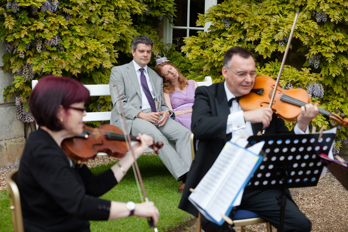 Wedding guests fallen asleep on a bench while listening to a string quartet
