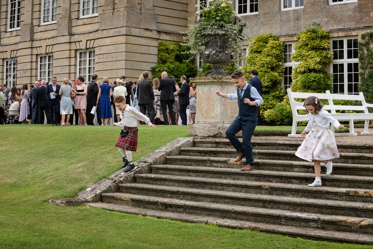 Children playing on steps during a wedding drinks reception