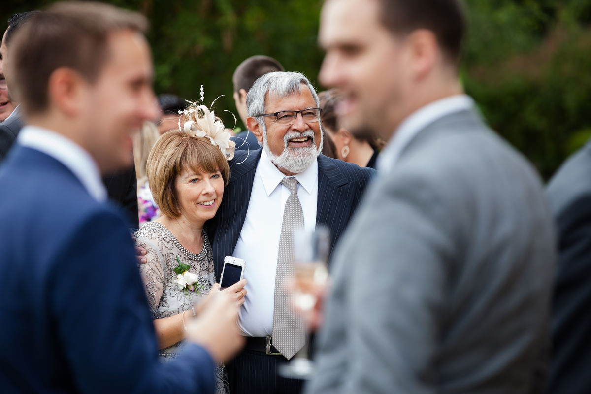 Wedding guests enjoying a drinks reception at Holdenby House