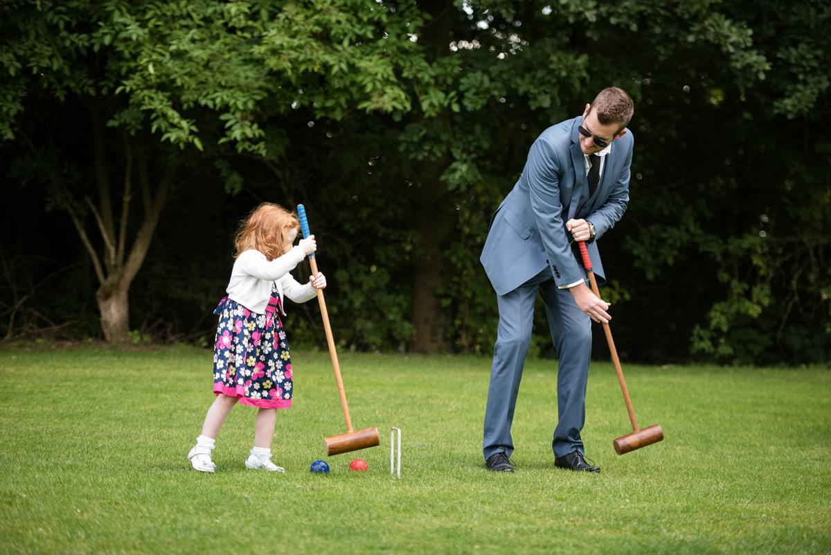 Dad teaching his daughter how to play croquet during a wedding drinks reception