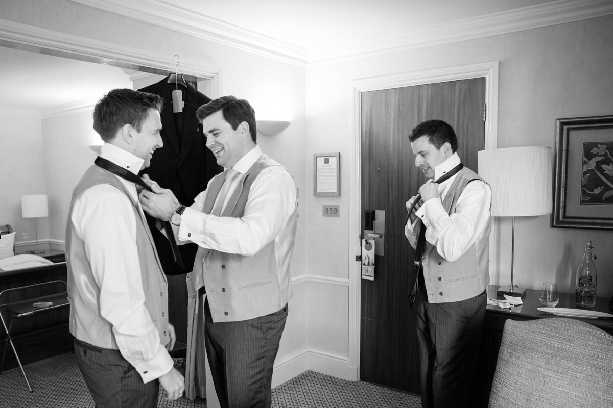 Groom, his best man and usher putting their ties on