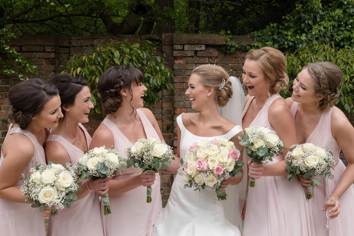 Bride laughing with her five bridesmaids wearing pale pink dresses