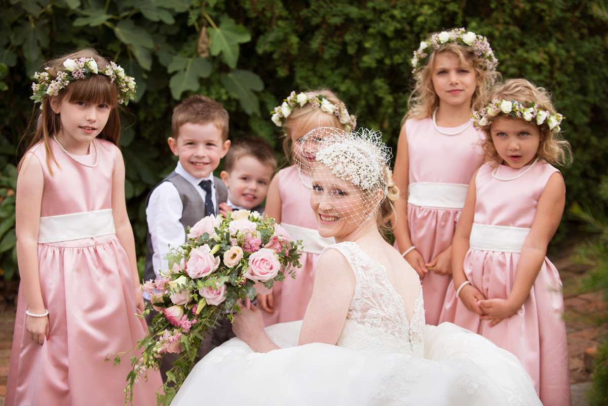 Bride wearing birdcage veil with her flower girls and page boys