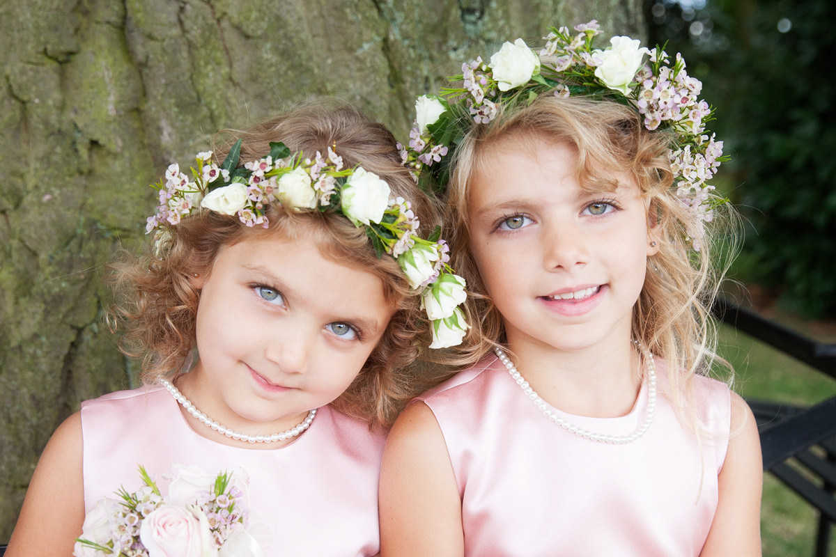 Two flower girls in pink dresses and fresh flower crowns