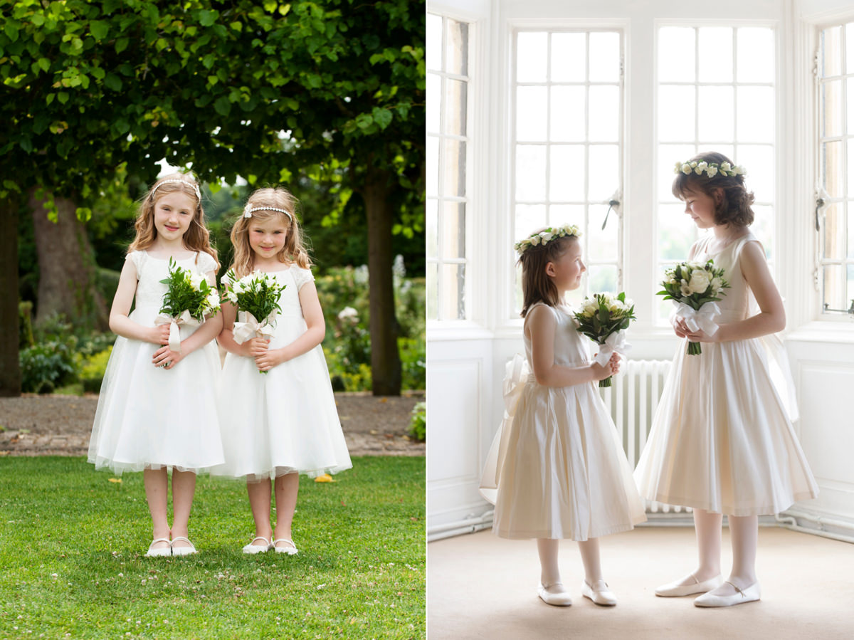 Flower girls wearing white dresses and carrying white & greenery bouquets