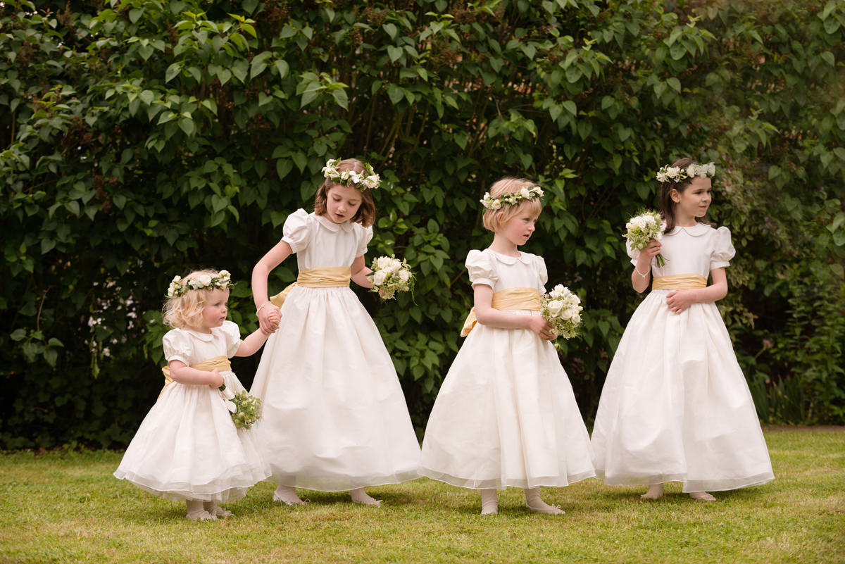 Four flower girls with white flower crowns, ivory dresses and dusty yellow sashes