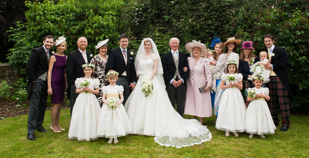 Bride and groom with both of their families and bridal party