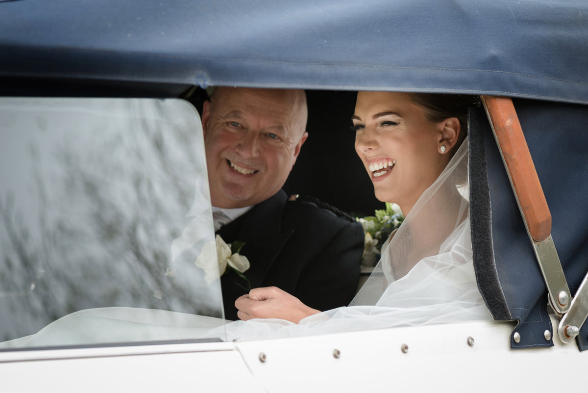 The bride and her dad in the wedding car as they arrive at church
