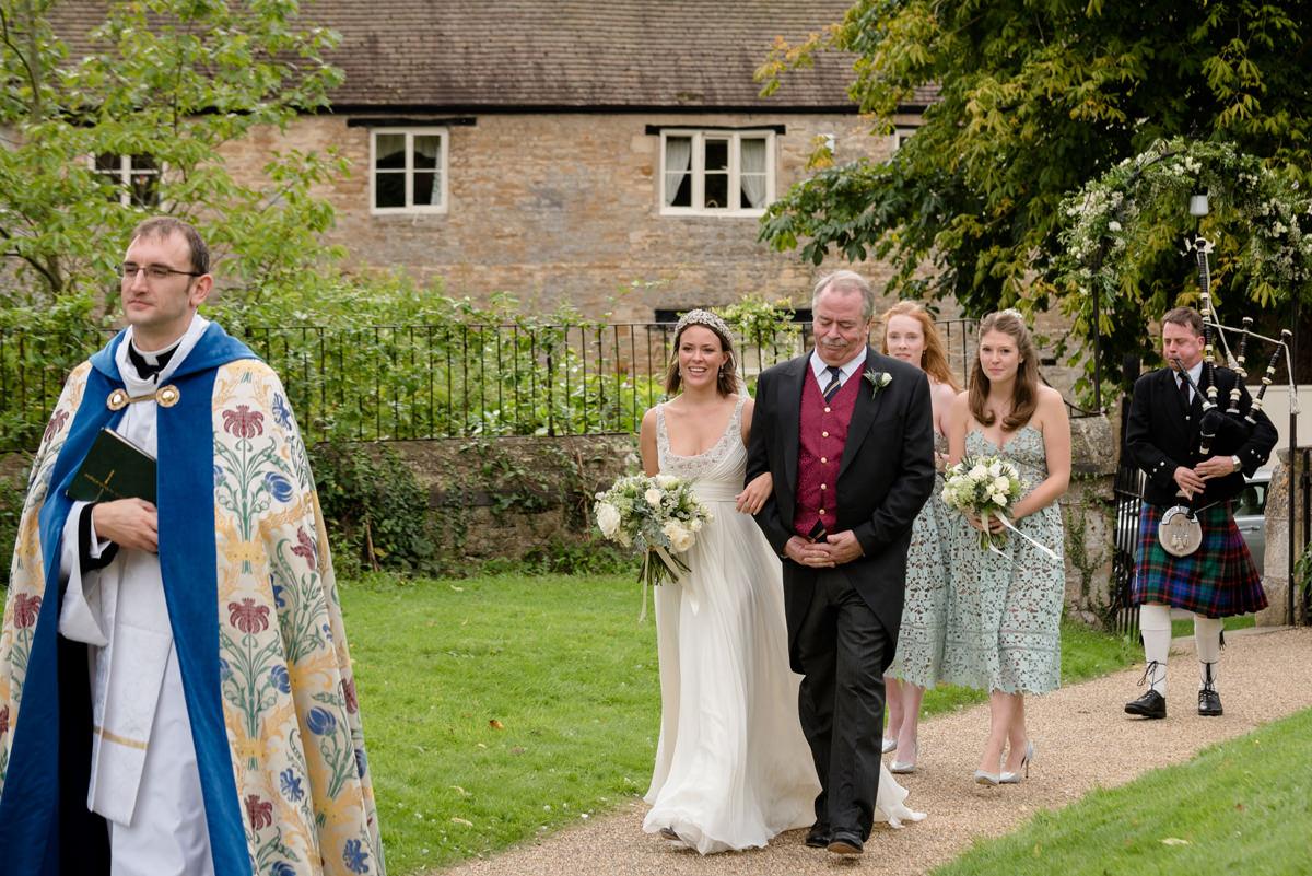 A bride walking down the church path with a bagpiper