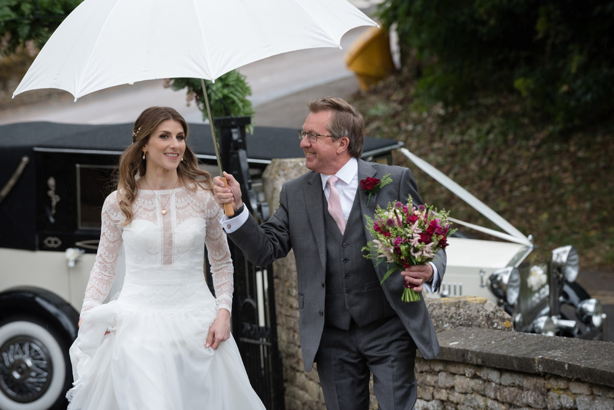 A bride and her dad arriving at church in the rain