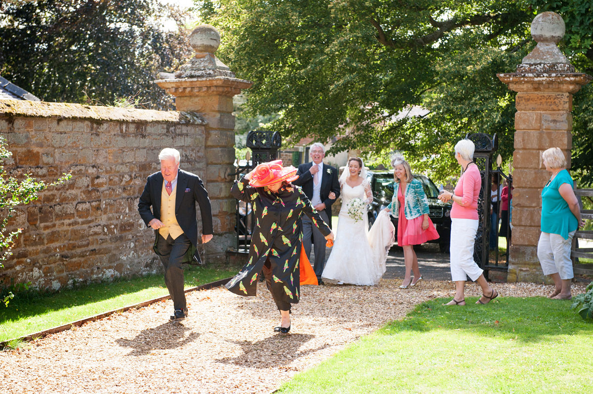 Two late wedding guests running past the bride as she arrives at church